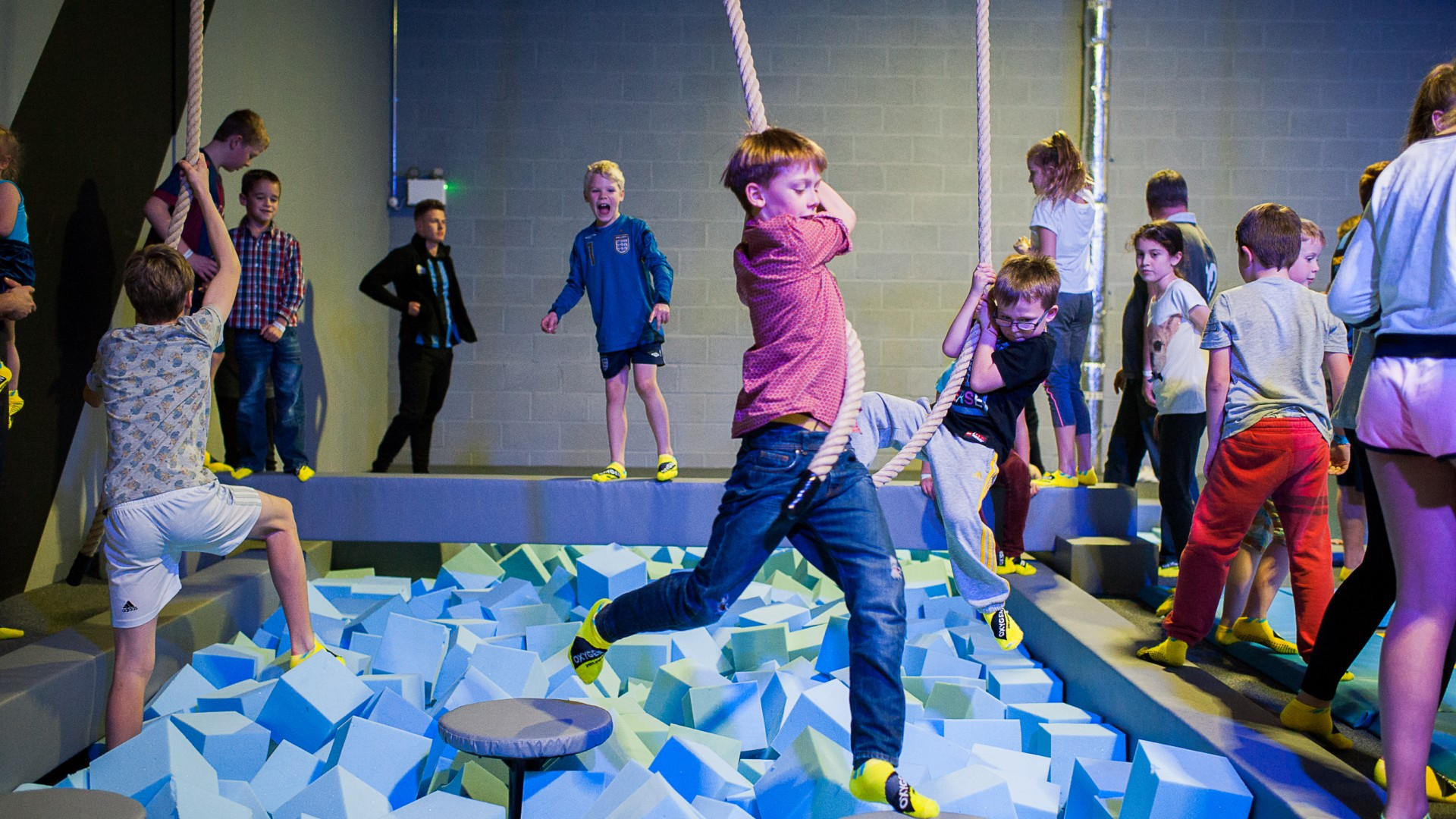 boy swinging on rope in the obstacle course at Oxygen Freejumping trampoline park