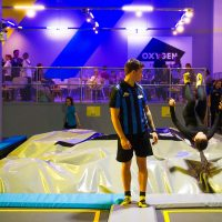 Girl somersaulting into giant pit in trampoline park