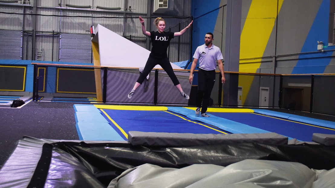 instructor watches as girl jumps on trampoline and into airbag