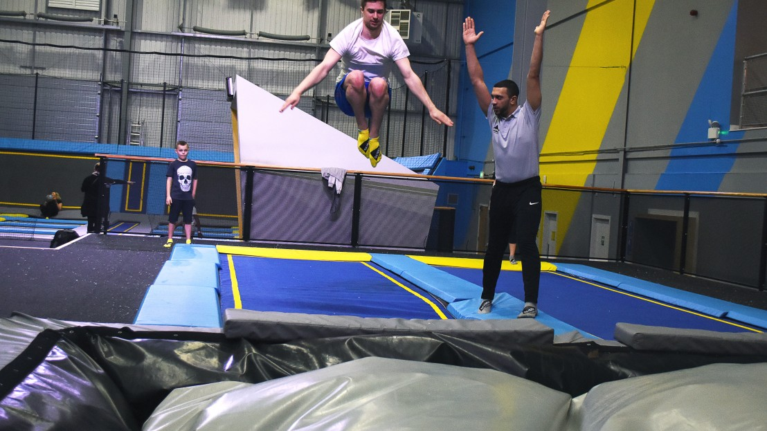 instructor teaches boy how to flip from trampoline to airbag