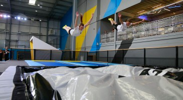 Two people jumping synchronised in trampoline park