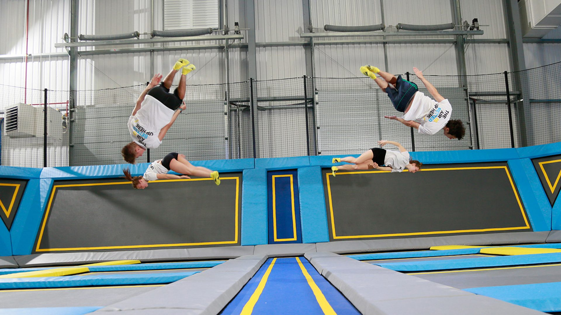 Four people somersaulting in trampoline park