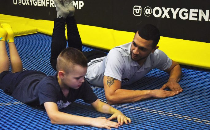 Man and boy on trampoline coaching