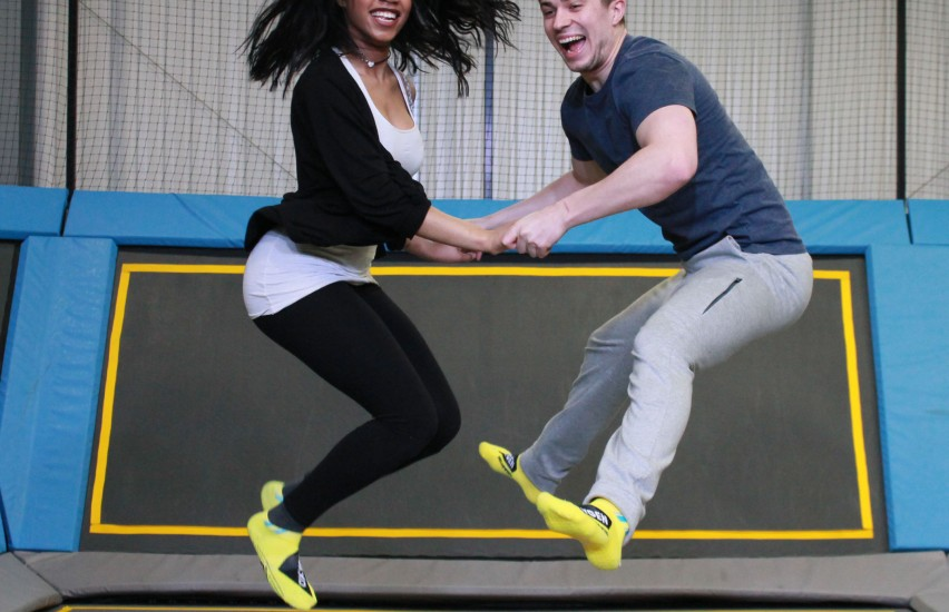 couple jumps on trampoline together at oxygen