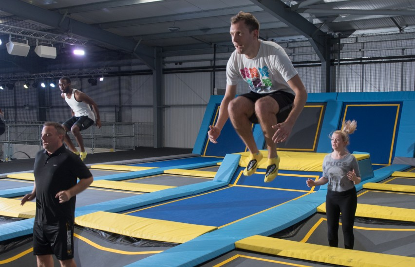 man bounces during trampoline fitness class