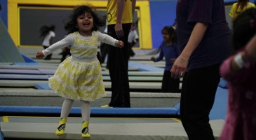 Girl in trampoline park jumping and laughing on trampoline